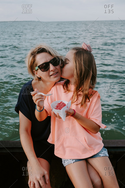 Adorable little girl holding bowl with fresh berries and kissing happy mother while sitting together on fence near sea during summer holidays