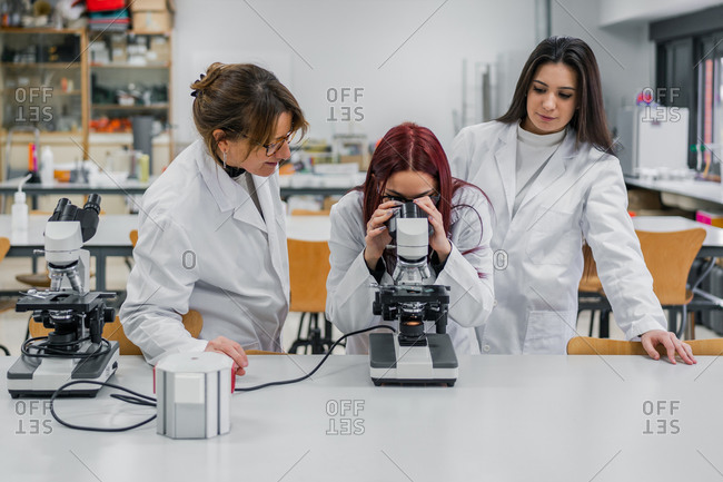 Female scientist inspecting tissue sample with contemporary microscope near coworkers while working in modern lab