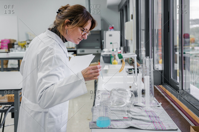 Side view of mature female scientist with clipboard examining glassware while working in modern chemistry laboratory