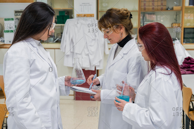 Female chemists working with liquids in lab
