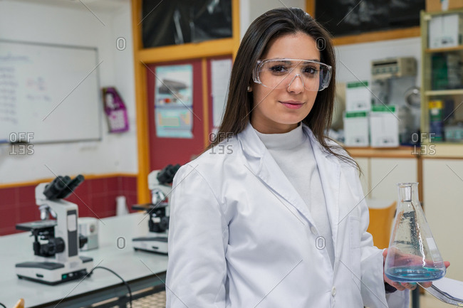Young woman in white coat and protective goggles carrying flask with chemical liquid and looking at camera while working in modern lab