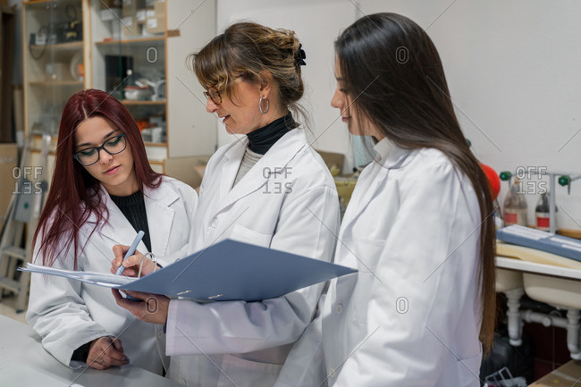 Mature woman in white coat writing experiment report near young female students during work in contemporary lab