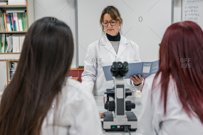 Mature woman teaching students in lab