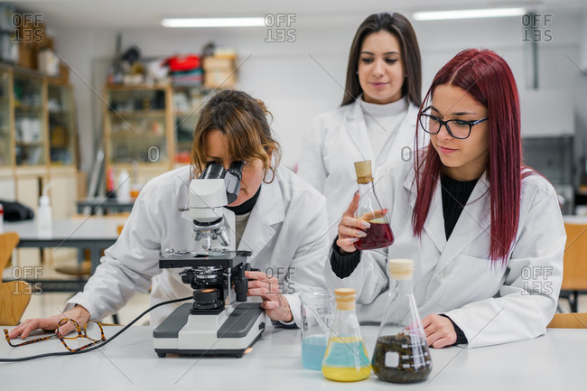 Adult woman examining sample in microscope near young women with chemical liquids during university lesson in modern lab