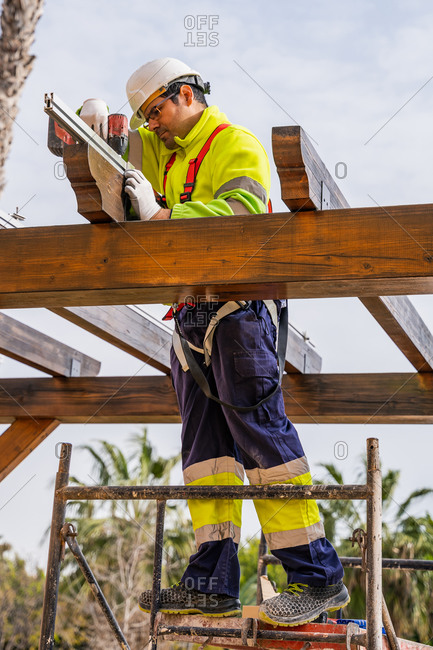 From below of male technician in work wear standing on scaffolding and preparing for installation of solar panel on wooden construction
