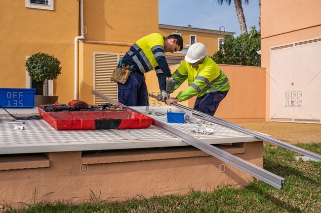 Group of male technicians in uniform working with alternative solar panels and preparing for installation near residential building