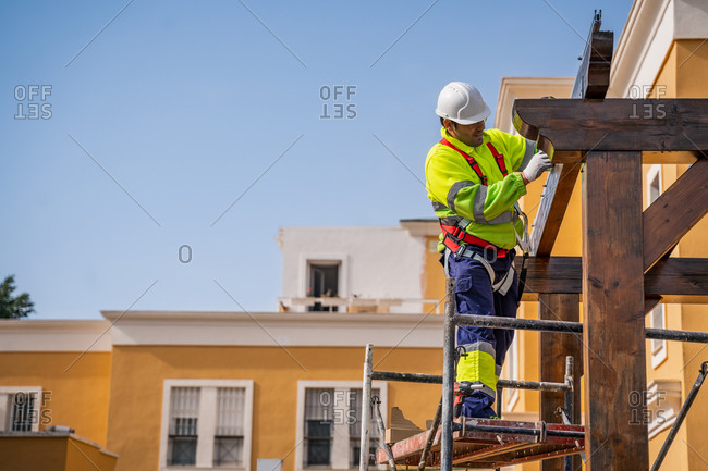From below side view of male technician in work wear standing on scaffolding and preparing for installation of solar panel on wooden construction