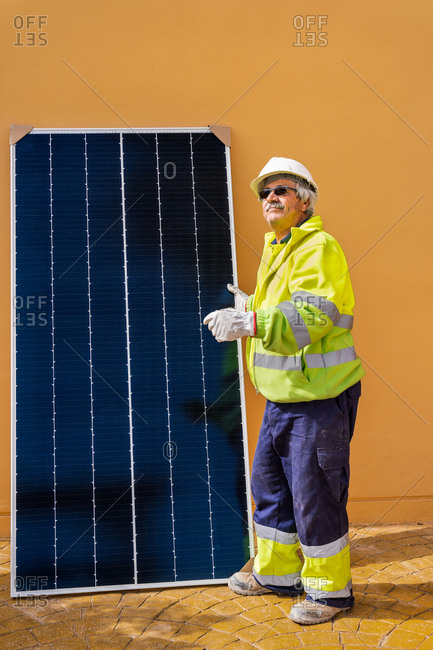 Side view of mature experienced male technician in uniform and helmet standing with solar panel near yellow building while working on installation of renewable energy system