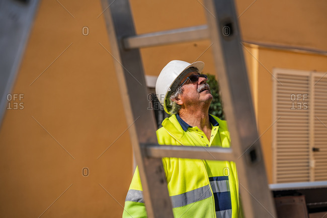 Positive skilled gray haired workman in uniform and protective helmet looking away while standing behind metal construction against building wall in sunny day