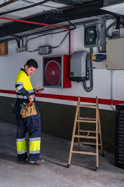 Side view of skilled man engineer in uniform using mobile phone while examining electrical equipment in modern building