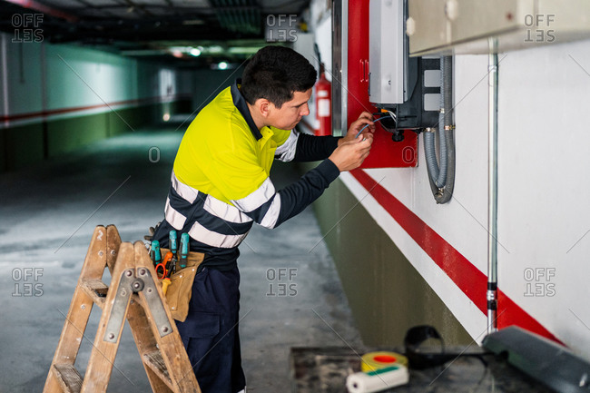 Side view of young professional male technician with electric tools repairing and checking equipment while working in building