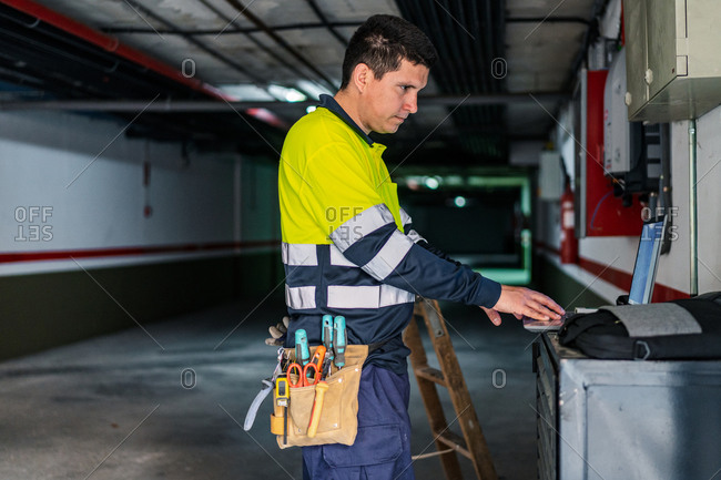 Side view of skilled man engineer in uniform using gadgets while examining electrical equipment in modern building