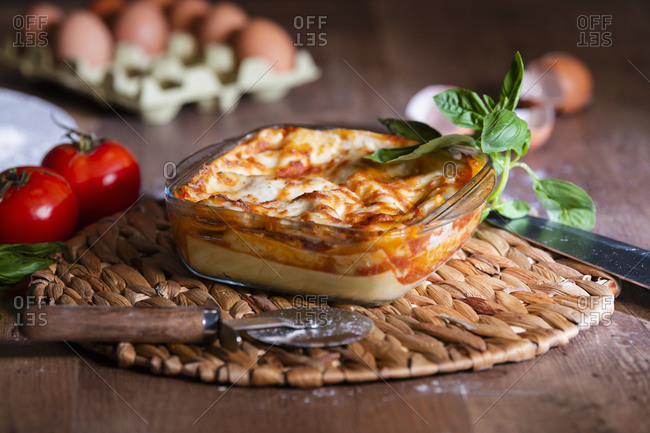 Delicious baked lasagna in glass bowl on table