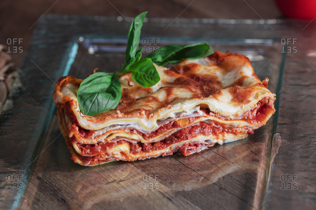 Delicious baked lasagna in glass dish on table
