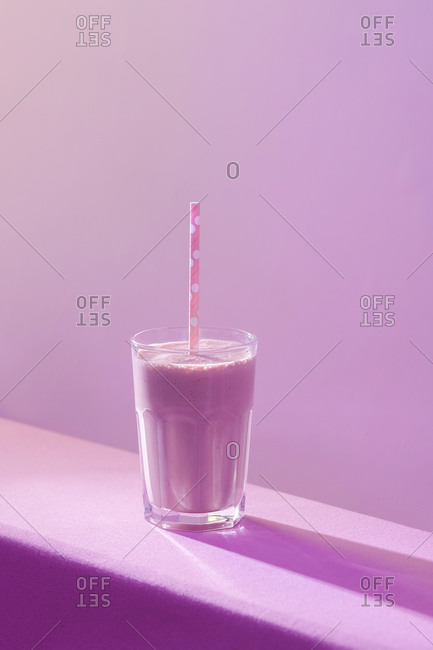 High angle of healthy delicious dairy beverage with fresh berries in transparent glass with straw on table in vivid purple light
