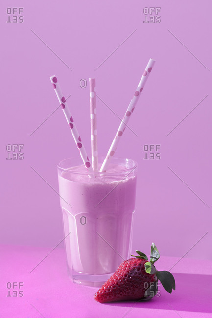 Yummy milkshake with fresh ripe strawberry on table in pink light