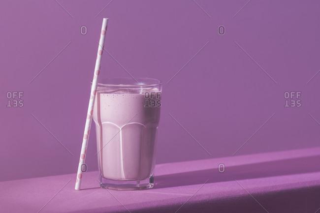 Tasty strawberry milkshake on table in pink light