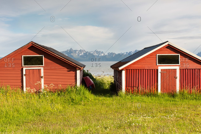 Red wooden buildings located on green meadow on shore with rocky mountains and cloudy sky in background in sunny day in countryside