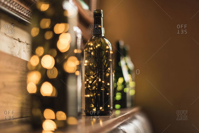 Composed transparent glass bottles with sparkling light garlands inside placed in row on wooden shelf near wall