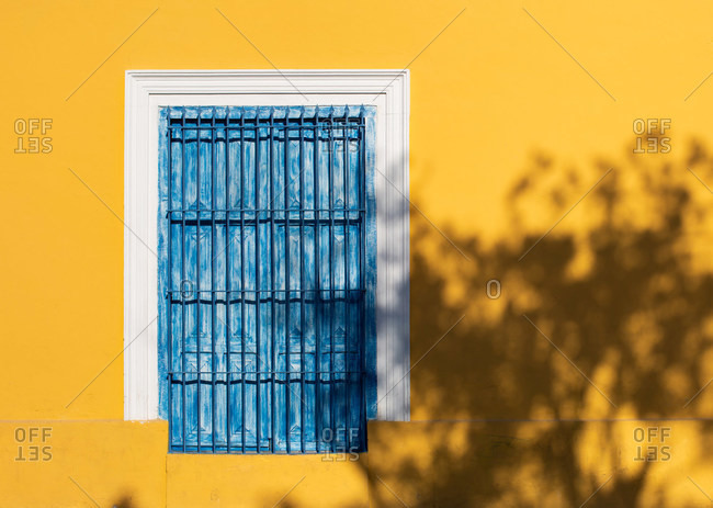 Shut window with shabby blue wooden shutters on bright yellow wall of building in sunshine