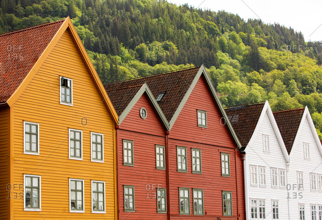Exterior of colorful low rise residential townhouses built in row against hill covered with green trees in summer day in suburbs