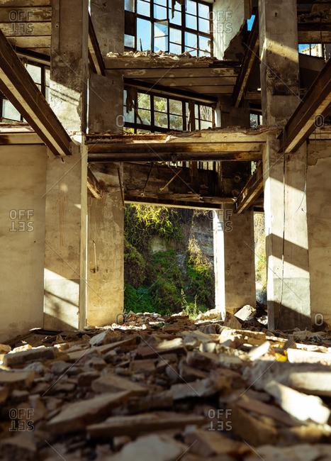 Low angle inside of aged abandoned disrupted city building with trash on floor lightened by sun rays