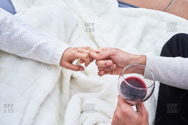From above side view of cheerful young couple in casual wear toasting with glasses of red wine while enjoying happy moments together