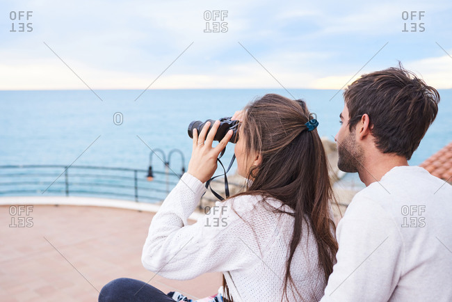 Side view of cheerful romantic couple in casual wear sitting on terrace with binoculars and enjoying view while spending holidays together at seaside