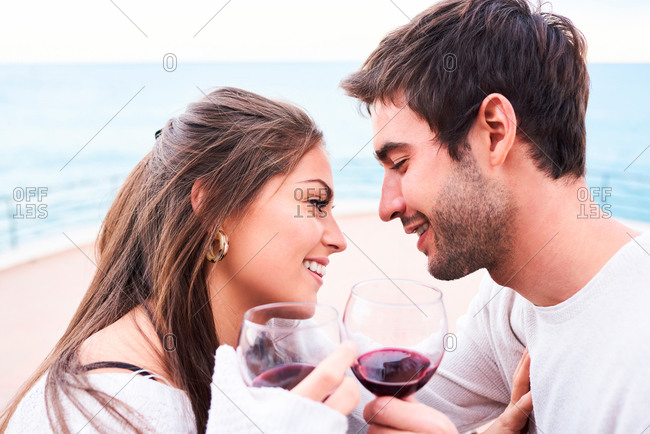 cheerful young couple in casual wear toasting with glasses of red wine while enjoying happy moments together