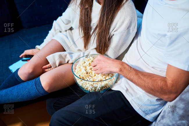 close-up a couple eating popcorn sitting on the sofa at home