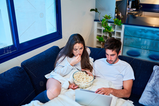 From above of cheerful young man and woman in casual wear eating popcorn and watching film on laptop while resting together on cozy sofa at home
