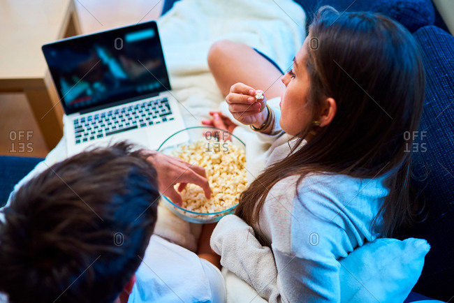 cheerful young man and woman in casual wear eating popcorn and watching film on laptop while resting together on cozy sofa at home