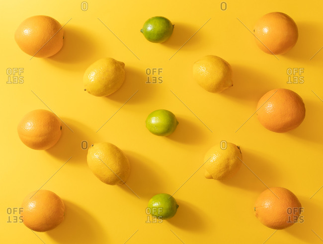 Top view of various fresh citruses on colorful yellow background