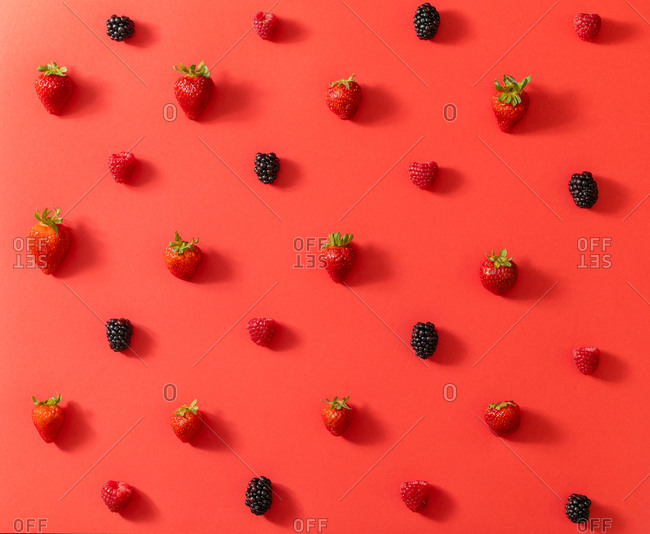 From above top view of fresh blackberry placed in line with ripe strawberries in summer berries composition on red surface background
