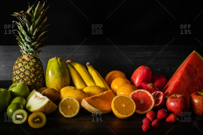 Bunch of various fresh fruits full of vitamins placed on black lumber table