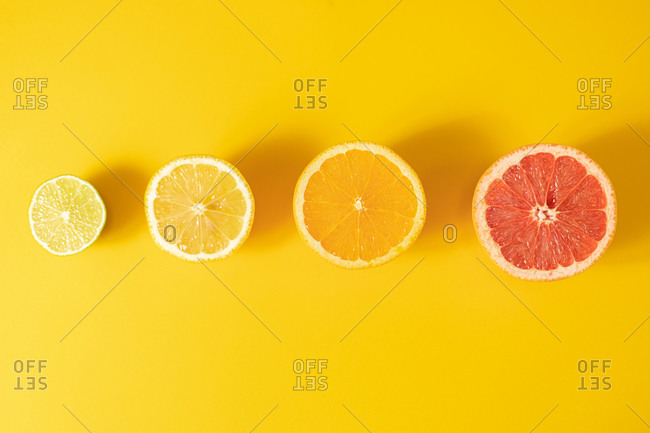 Top view of halves of assorted ripe citruses arranged in line on a yellow surface background