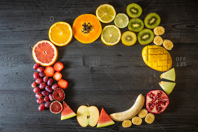 Top view of various peeled and cut healthy fruits and vegetables arranged in a circle on a black lumber table