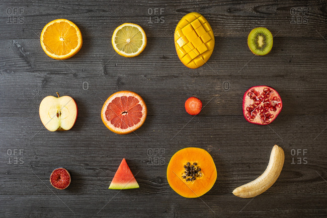 Top view of various peeled and cut healthy fruits and vegetables arranged on black lumber table