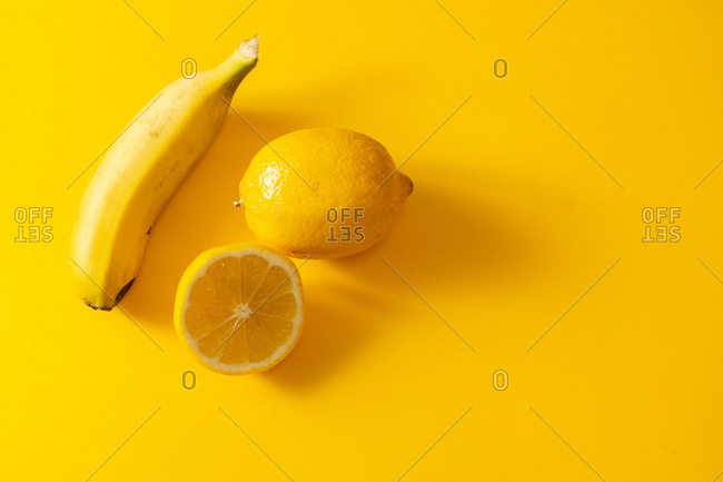 From above ripe banana and fresh lemon placed near one another on bright yellow background
