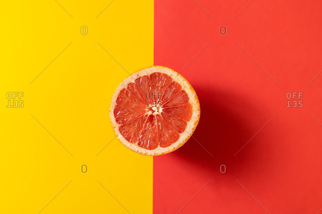 Top view of half of ripe grapefruit placed on line between yellow and red backgrounds