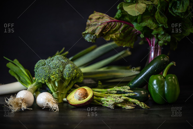 Bunch of various green vegetables placed on dark wooden table on black background