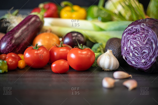 Heap of assorted fresh vegetables placed on black table during healthy food preparation in kitchen