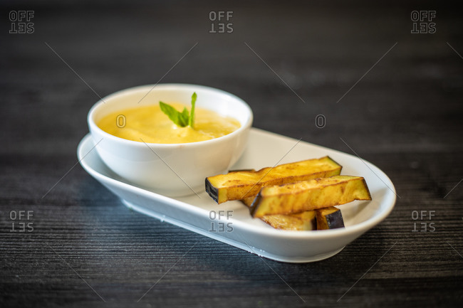 Bowl of delicious puree with herb placed on ceramic plate near pieces of fried eggplant on black wooden table in cafe