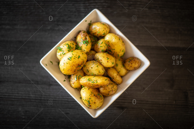 From above square bowl of yummy roasted potatoes with herbs placed on black timber table