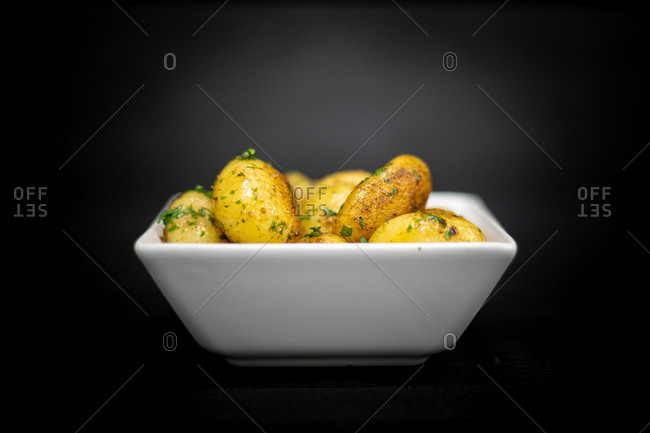 Square bowl of yummy roasted potatoes with herbs placed on black timber table
