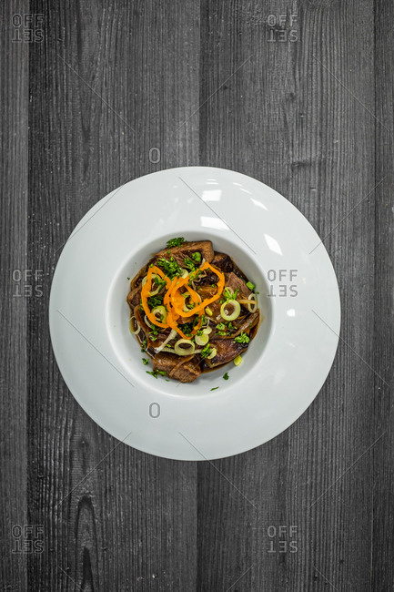 Top view of delectable fried meat served with sauce and herbs on ceramic plate on black wooden table