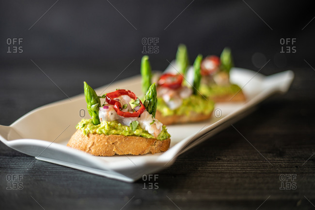 Closeup delicious small sandwiches with shrimp and vegetables placed on ceramic plate on black table in cafe
