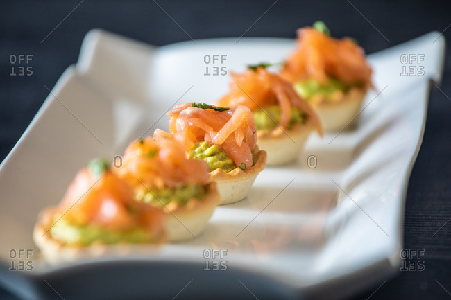 Closeup delicious tartlets with fish and guacamole arranged in row on ceramic plate in restaurant