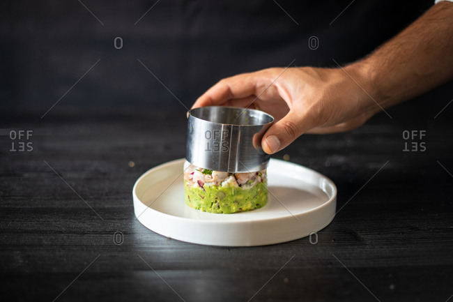 Crop chef using metal ring to form tasty healthy salad on ceramic plate on black table in restaurant