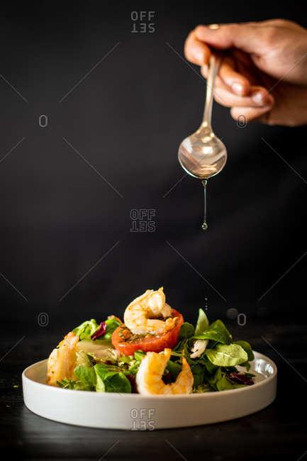 Unrecognizable cook adding spoonful of oil to yummy vegetable salad with shrimps on black background